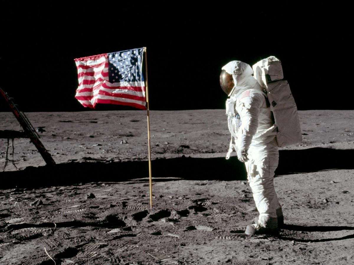 Neil Armstrong on the moon with the American flag.
