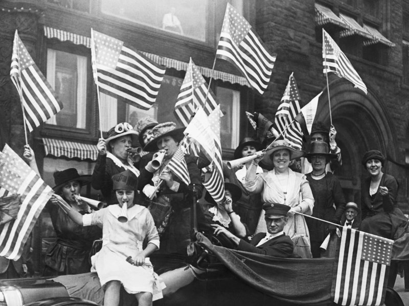 A black and white photograph of several women waving American flags.