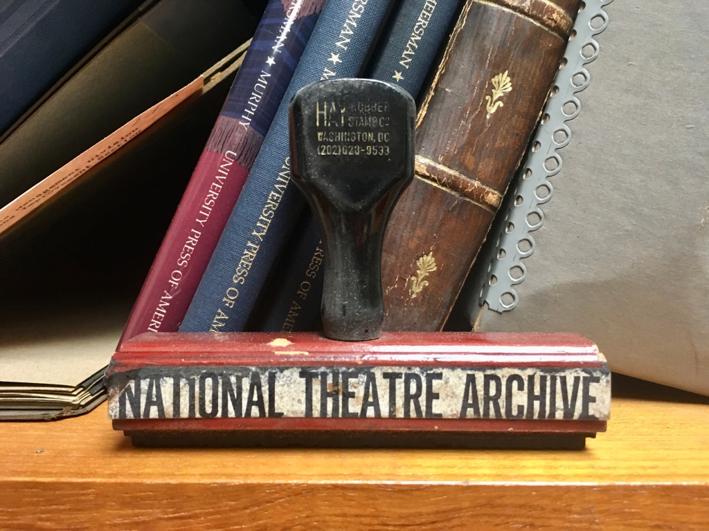 """A stamp with """"National Theatre Archive"""" written on it sits on a bookshelf."""